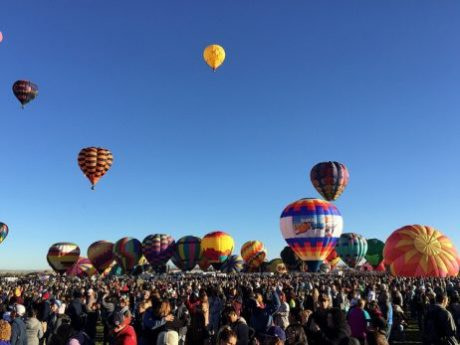 Balloons take flight as a crowd cheers